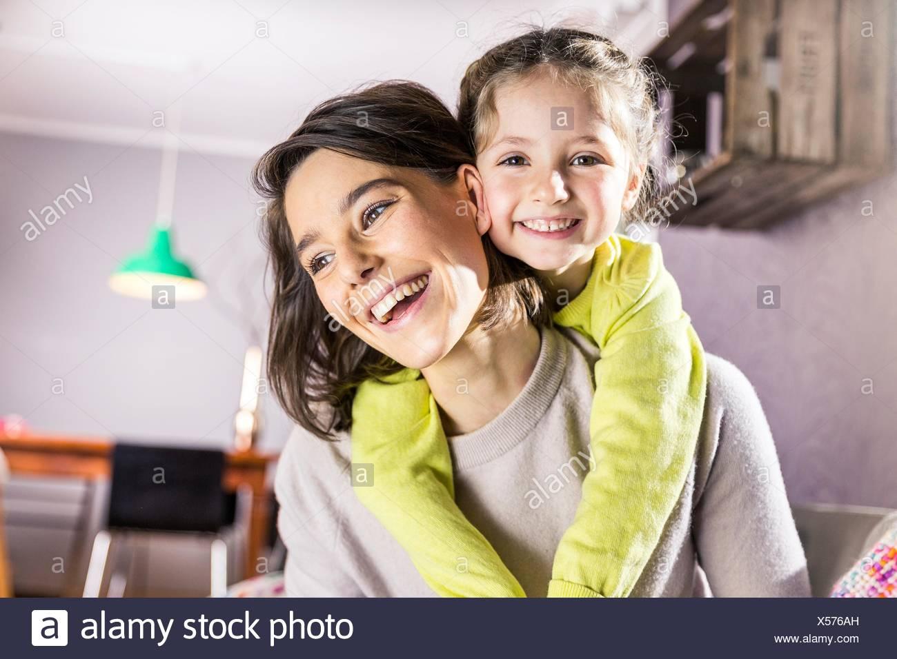 Retrato de niña obteniendo piggyback paseo de la madre en la sala de estar Imagen De Stock