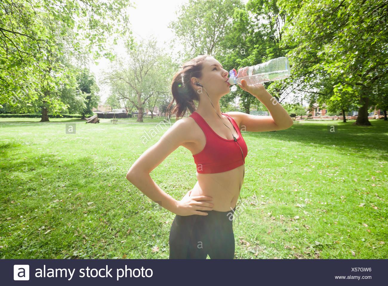 Colocar mujer agua potable mientras escucha música en el parque Imagen De Stock