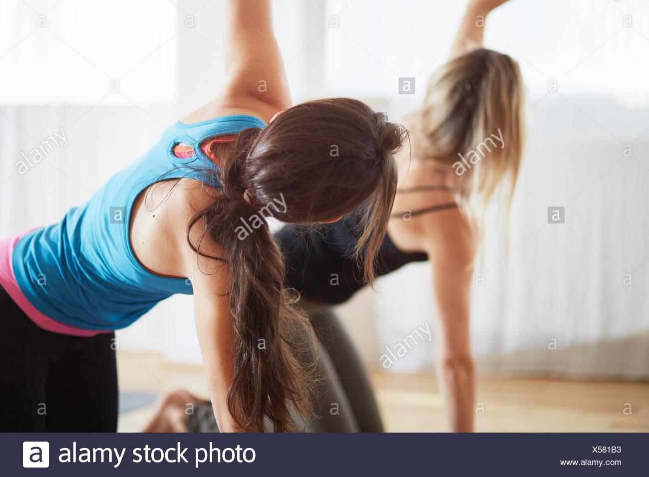 Dos mujeres de rodillas y elevando los brazos en clase de pilates Imagen De Stock