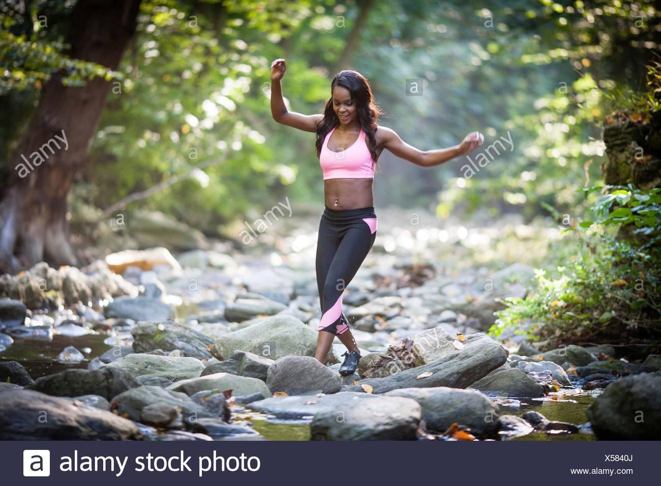 Mujer joven excursionista pisando sobre piedras de río de bosque Imagen De Stock