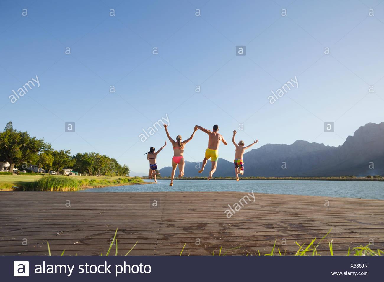 Familia saltar al lago desde un embarcadero Imagen De Stock