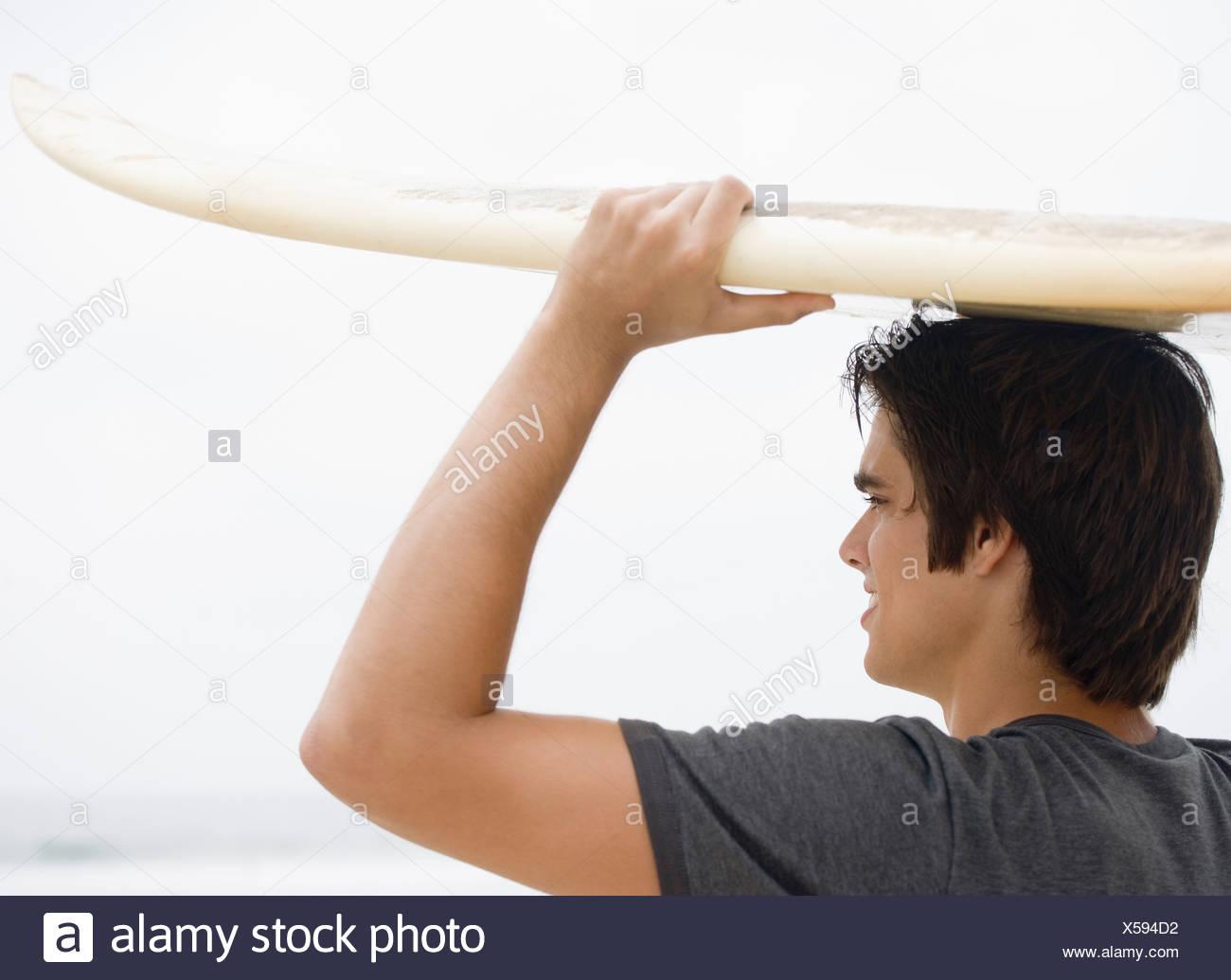 El hombre lleva las tablas de surf en la cabeza. Foto de stock