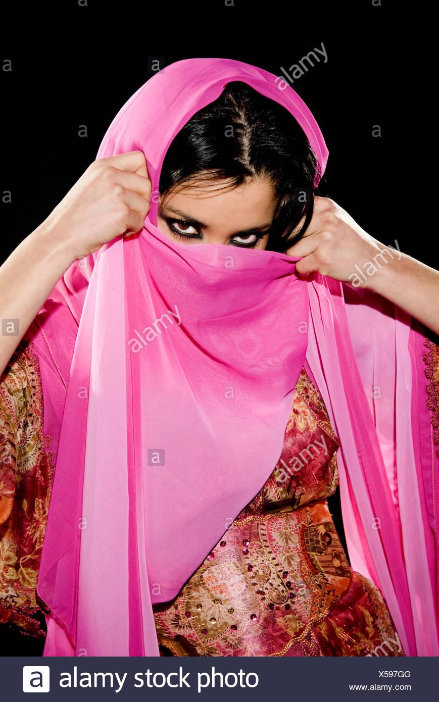 Arabian mujer vestida con un traje tradicional sobre fondo negro Imagen De Stock