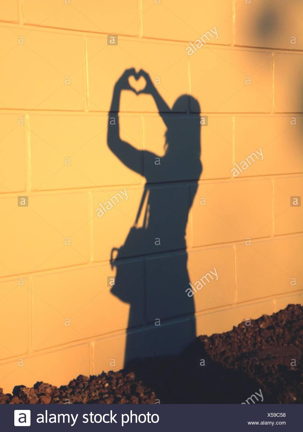 Sombra de Mujer formando corazón sobre la pared de azulejos Foto de stock