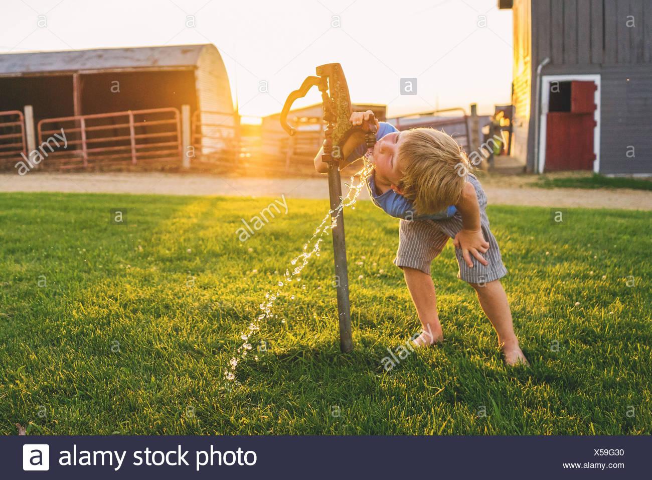Chico de beber agua de grifo en una granja Imagen De Stock