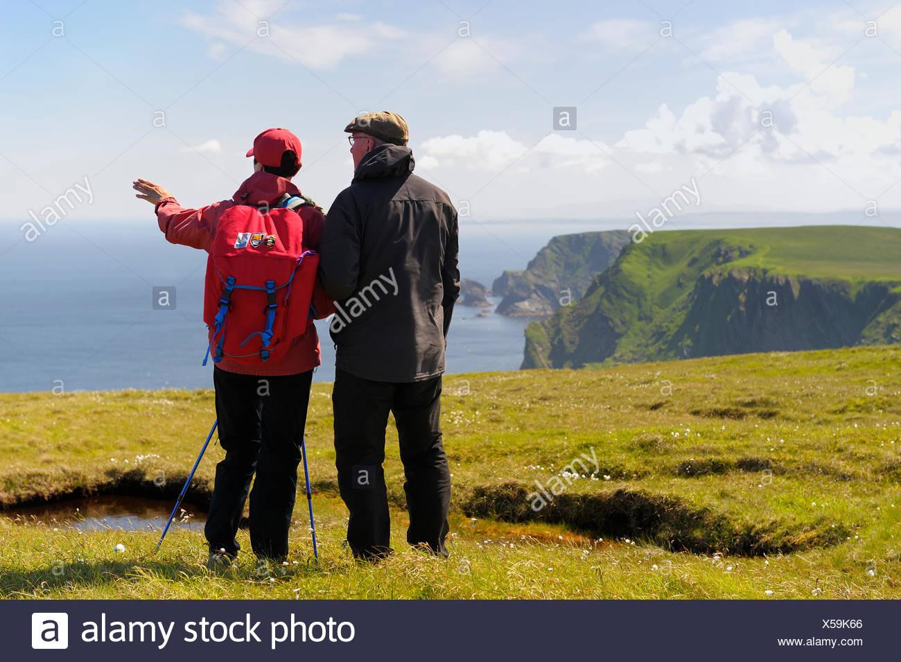 Reino Unido, Escocia, Islas Shetland, Unst, Hermaness, Senior Pareja mirando el mar desde el acantilado de hierba Imagen De Stock