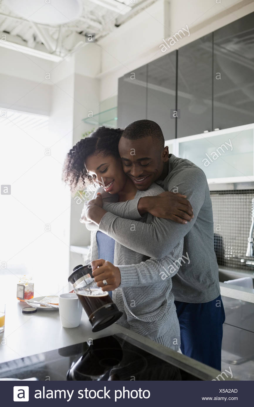 Pareja sonriente abrazando y verter el café de la mañana Imagen De Stock