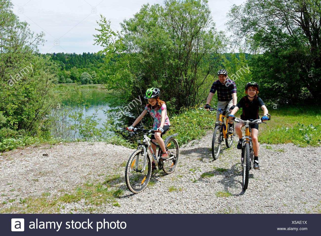 Viaje en Bicicleta, ciclistas montando sus bicicletas en Ickinger Stausee depósito, Pupplinger Au, el río Isar, la Alta Baviera, Baviera Imagen De Stock