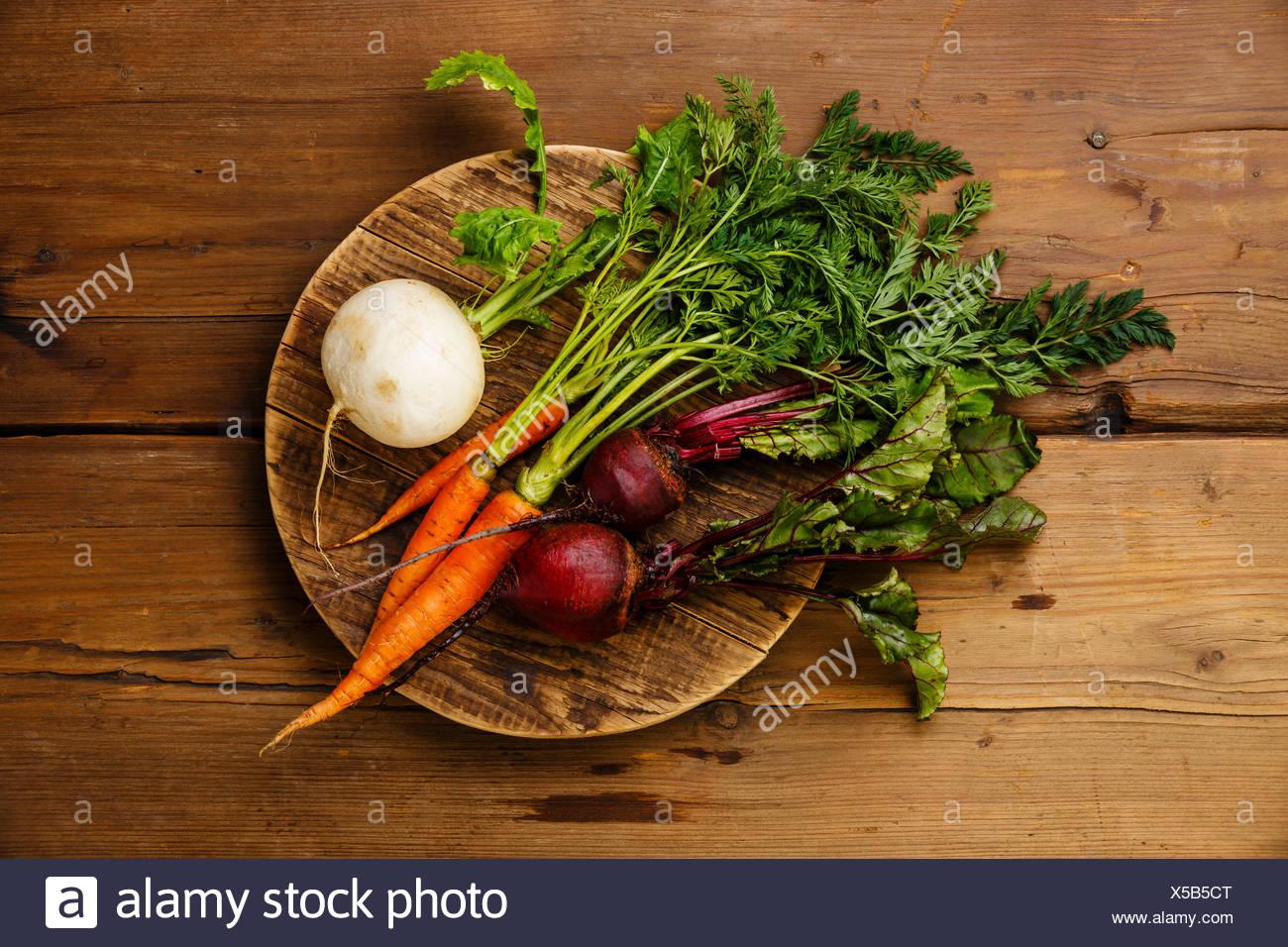 Hortalizas frescas las zanahorias, nabos y remolachas en junta de corte redondo sobre fondo de madera Imagen De Stock