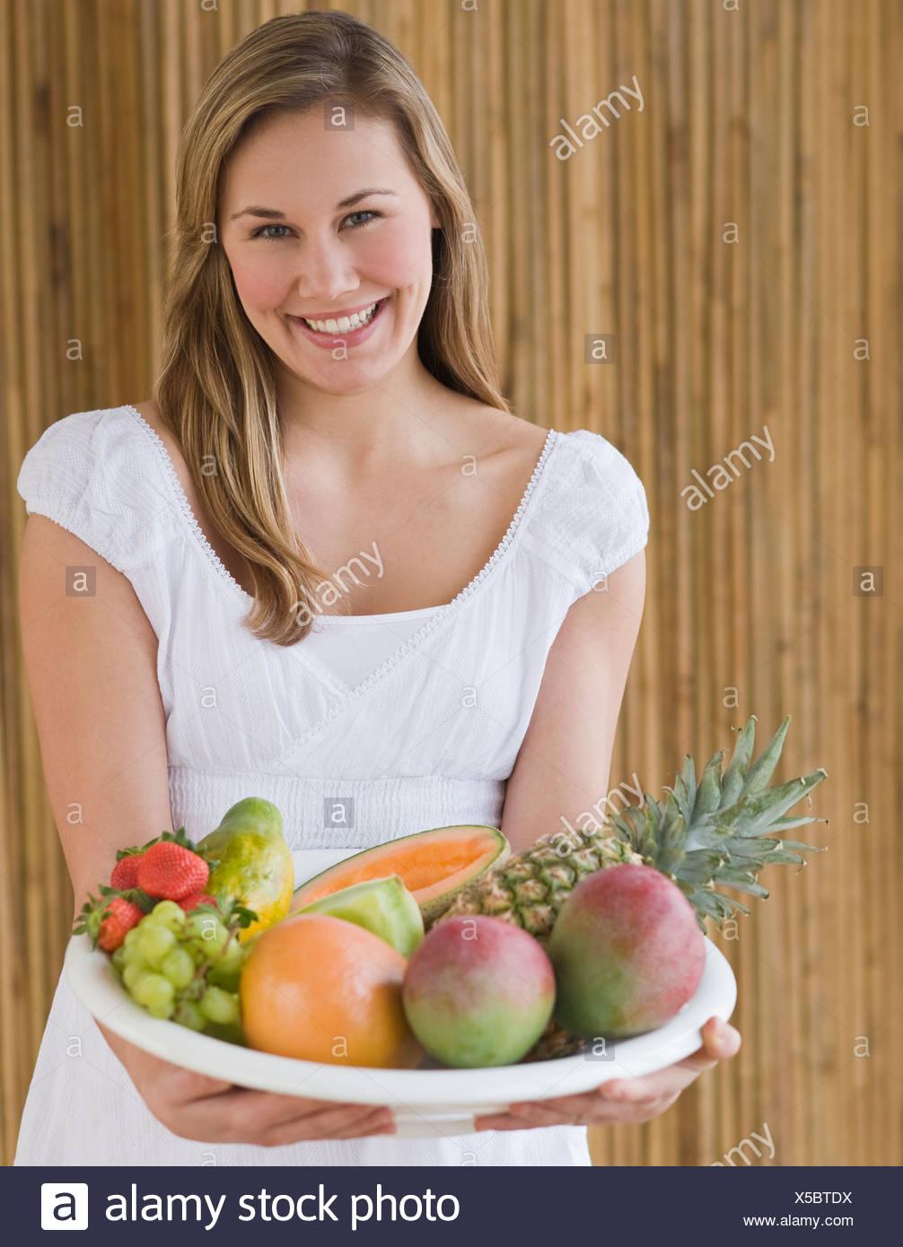 Mujer sosteniendo el tazón de fruta Imagen De Stock