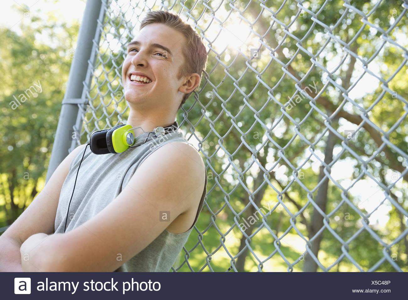 Adolescente sonriente apoyado en cercado de cadenas Imagen De Stock