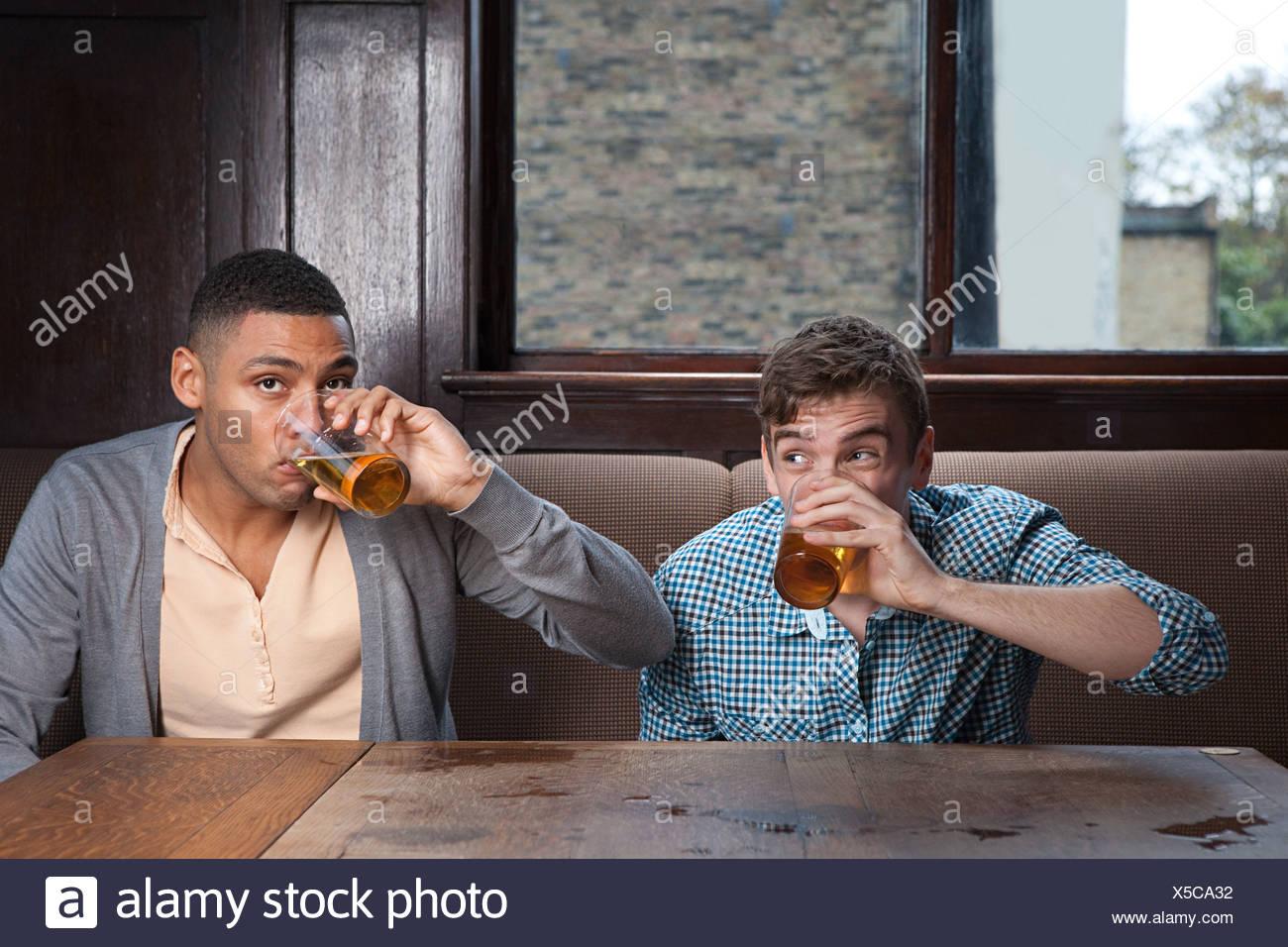 Los hombres jóvenes bebiendo cerveza en el bar Foto de stock