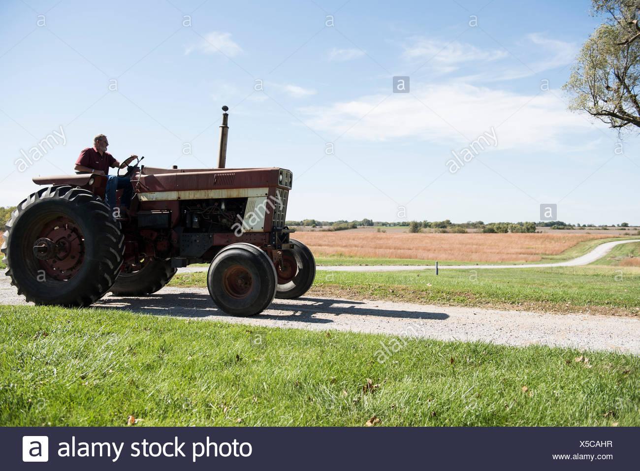 Agricultor manejando el tractor en carretera rural, Missouri, EE.UU. Imagen De Stock