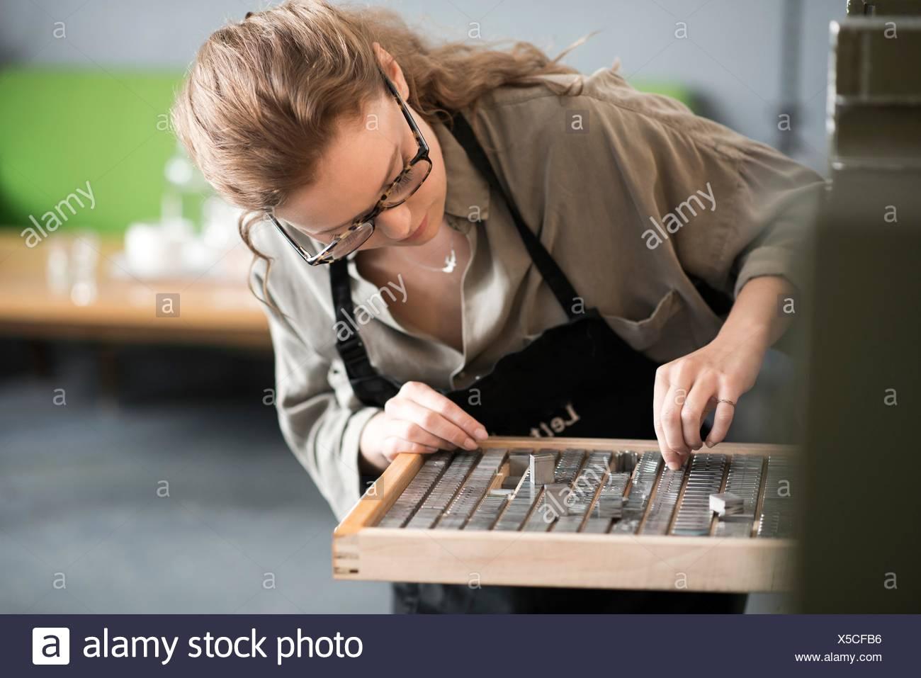 Mujer elegir tipografía de la bandeja en el taller de impresión Imagen De Stock