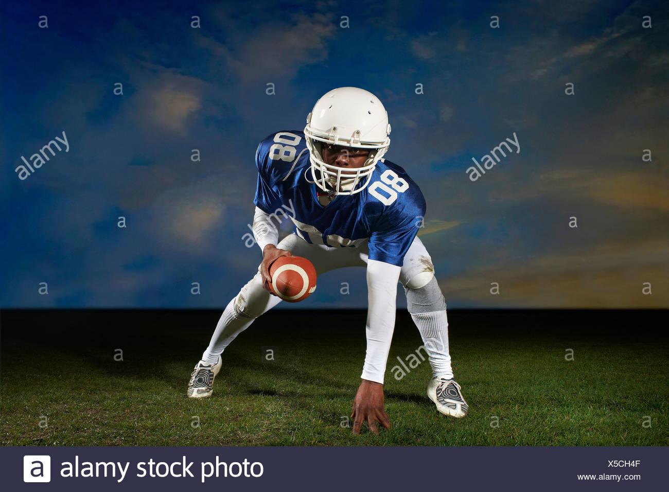 Jugador de fútbol americano se inclina hacia adelante con la mano sobre el césped Imagen De Stock