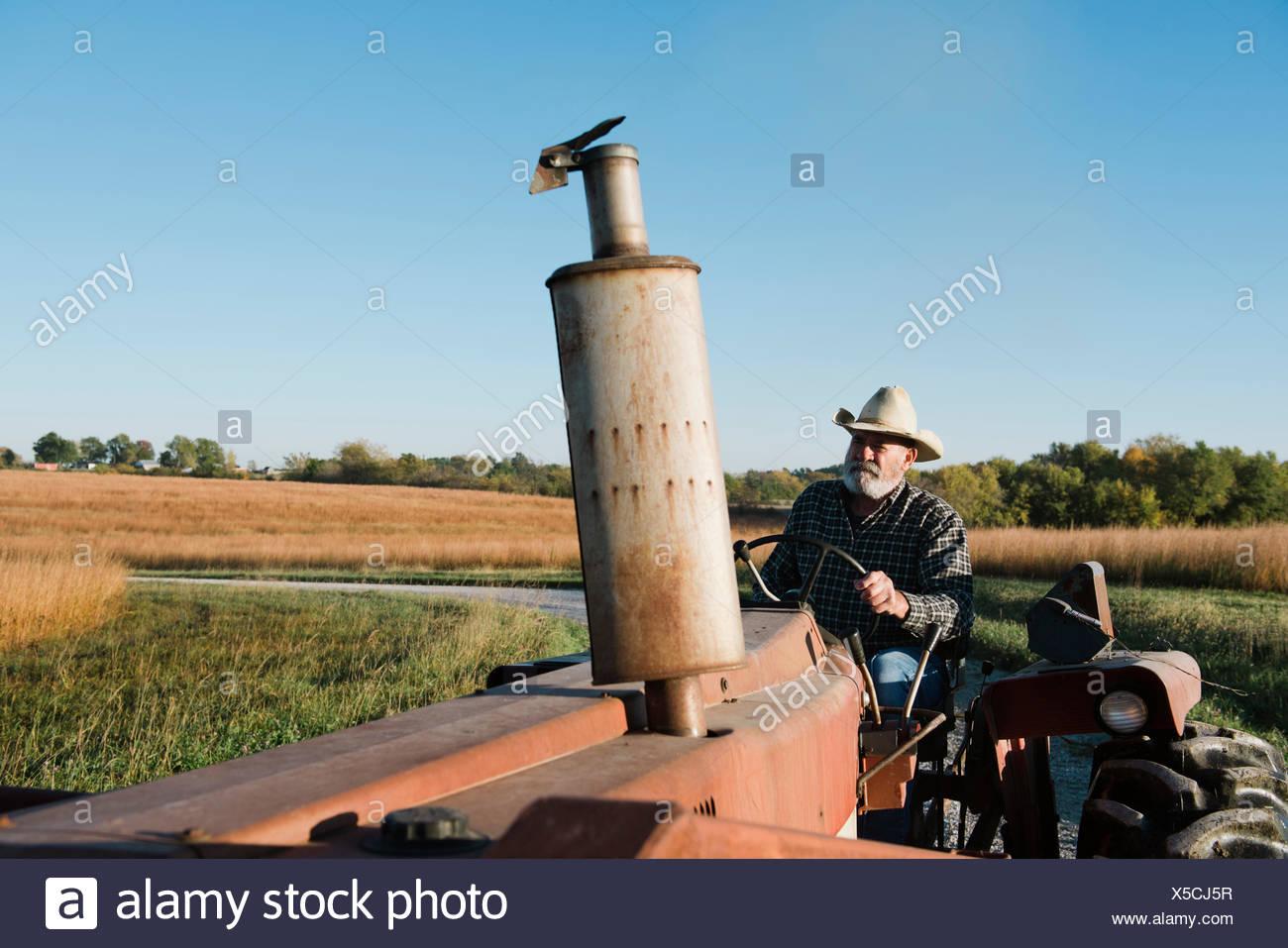 Altos agricultor conducción del tractor en carreteras rurales, Plattsburg, Missouri, EE.UU. Imagen De Stock