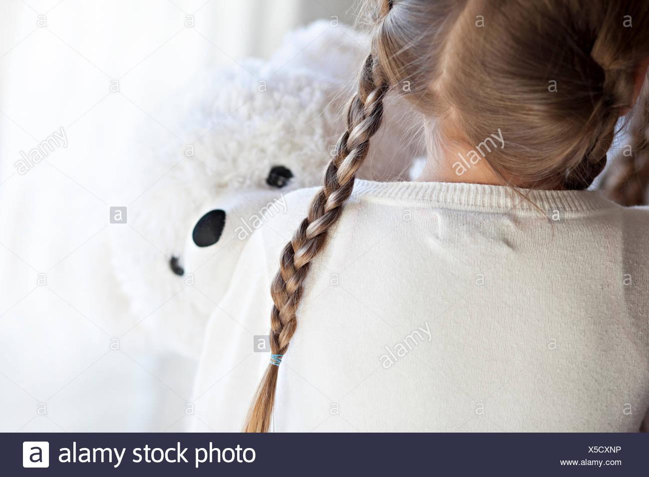 Vista trasera de una niña abrazando a un oso de peluche Imagen De Stock