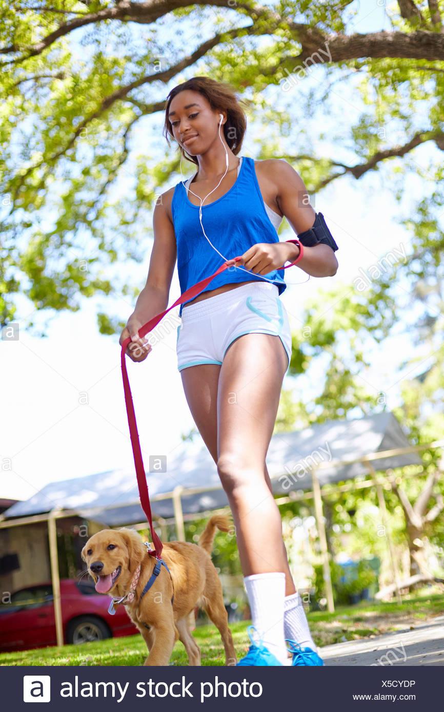 Mujer joven el ejercicio con el perro en el parque Imagen De Stock