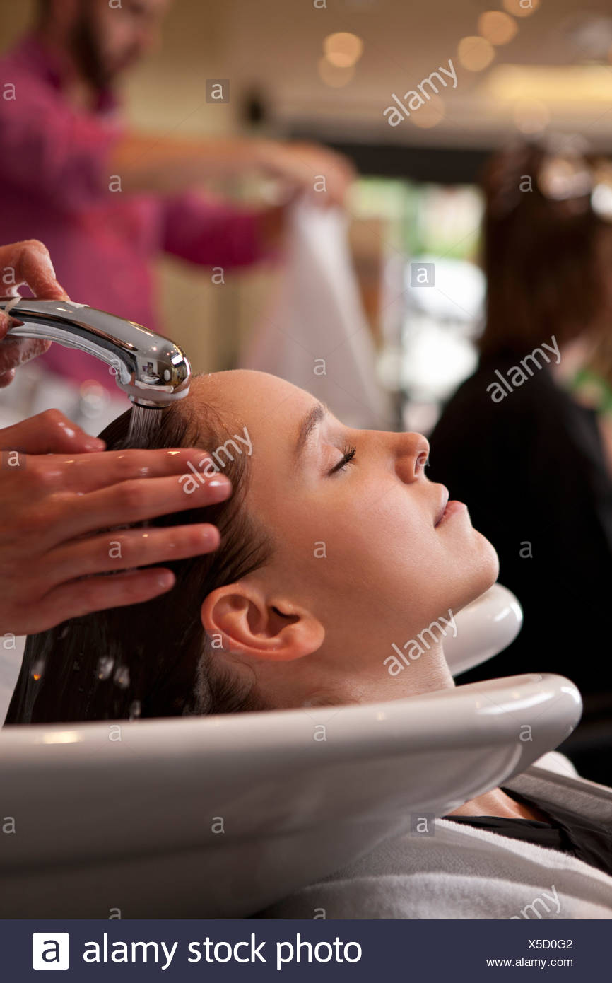Una clienta tener sus cabellos lavados en una peluquería, cerrar Imagen De Stock