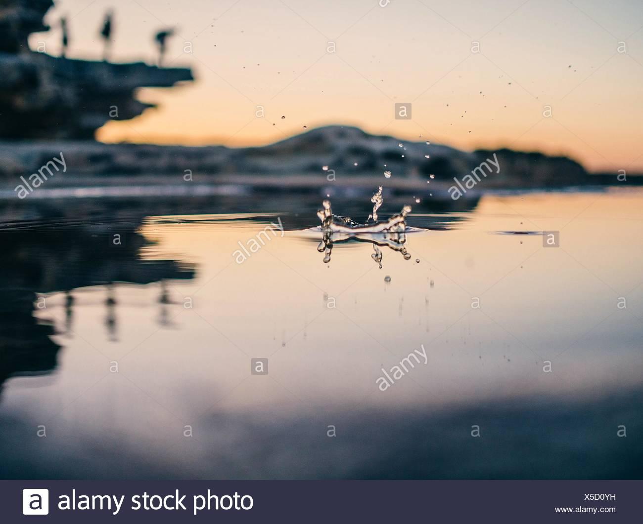 La superficie vista de gota caiga en el lago al atardecer Imagen De Stock