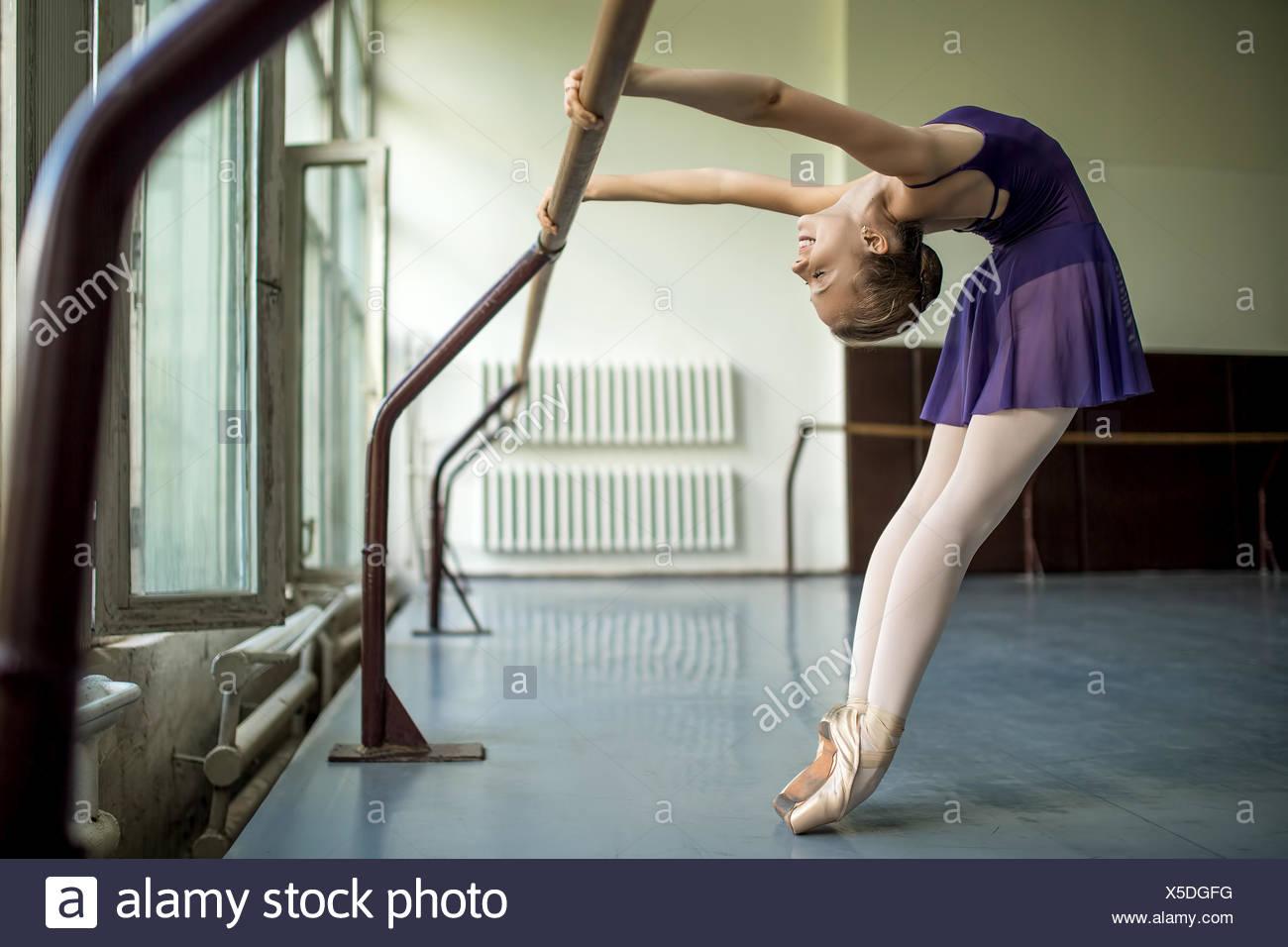 Joven bailarín haciendo un ejercicio en el aula cerca de Barre. Stretc Imagen De Stock