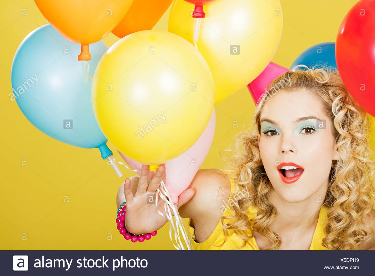 Joven Mujer rubia con globos contra el fondo amarillo Imagen De Stock