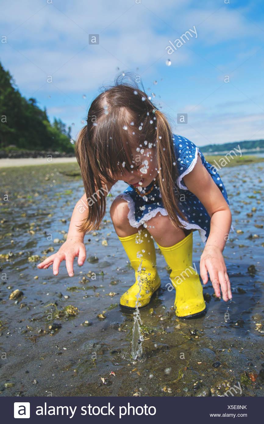 Chica chapoteando en el agua en la playa Imagen De Stock