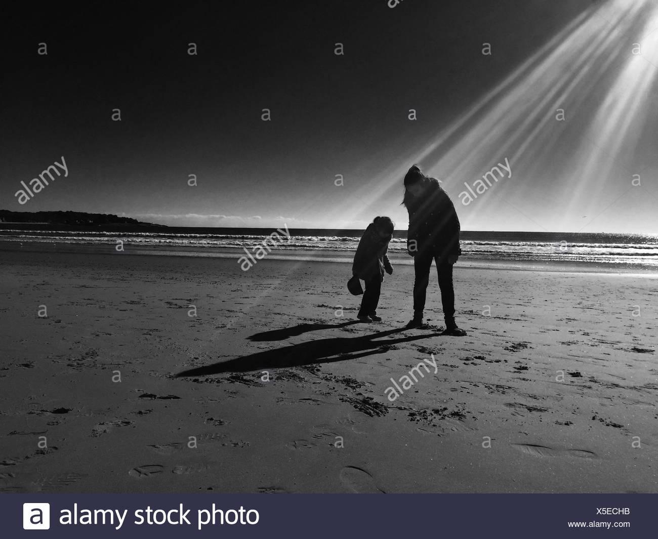 La madre con su hija de pie en la playa Imagen De Stock