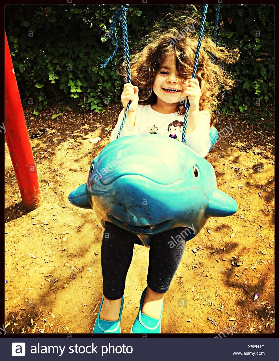 Chica disfrutando de paseo en columpio infantil Imagen De Stock