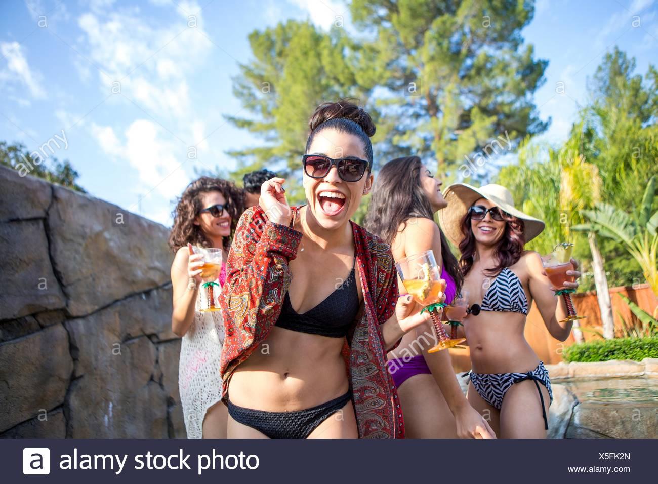 Mujer joven con hermanas y hermanos de beber cócteles en el jardín Imagen De Stock