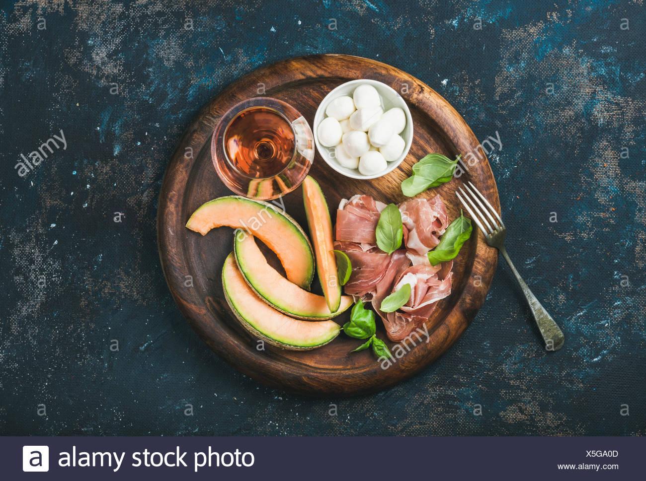 Prosciutto di Parma, melón, queso mozzarella en un recipiente, hojas de albahaca fresca y una copa de vino rosado en round serving tra Imagen De Stock