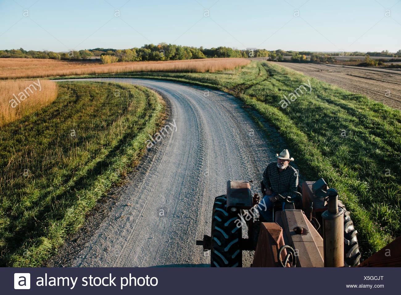 Un alto ángulo de visualización de altos agricultor conducción del tractor en carreteras rurales, Plattsburg, Missouri, EE.UU. Imagen De Stock