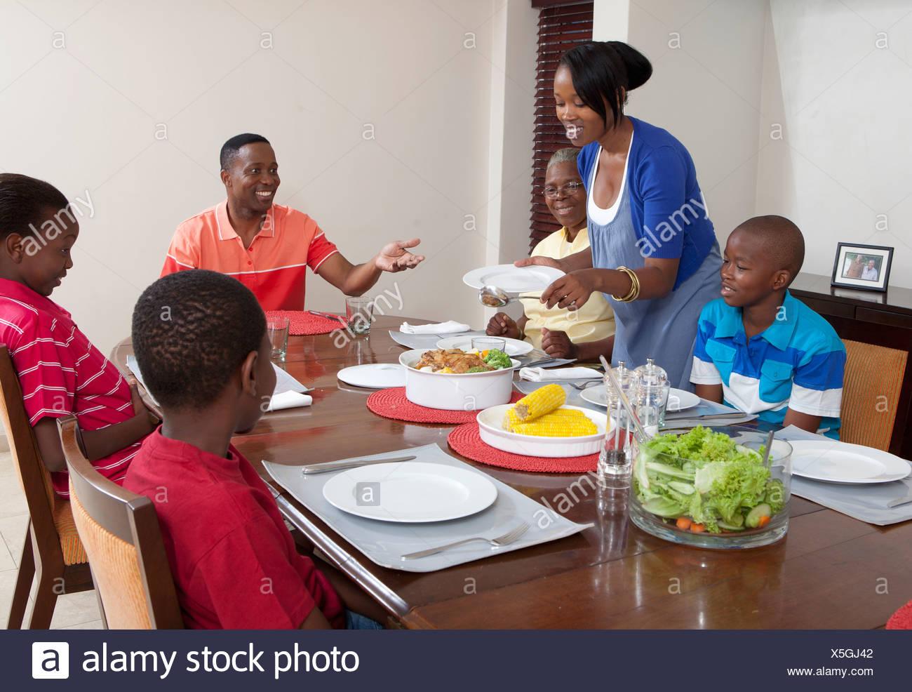 Madre sirviendo comida en la mesa de comedor, Johannesburgo, Sudáfrica Imagen De Stock