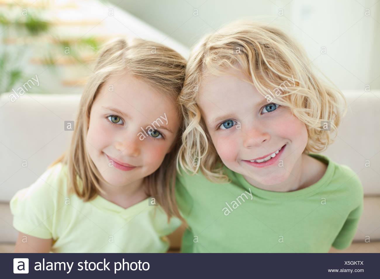 Hermanos sonriente en el sofá Imagen De Stock