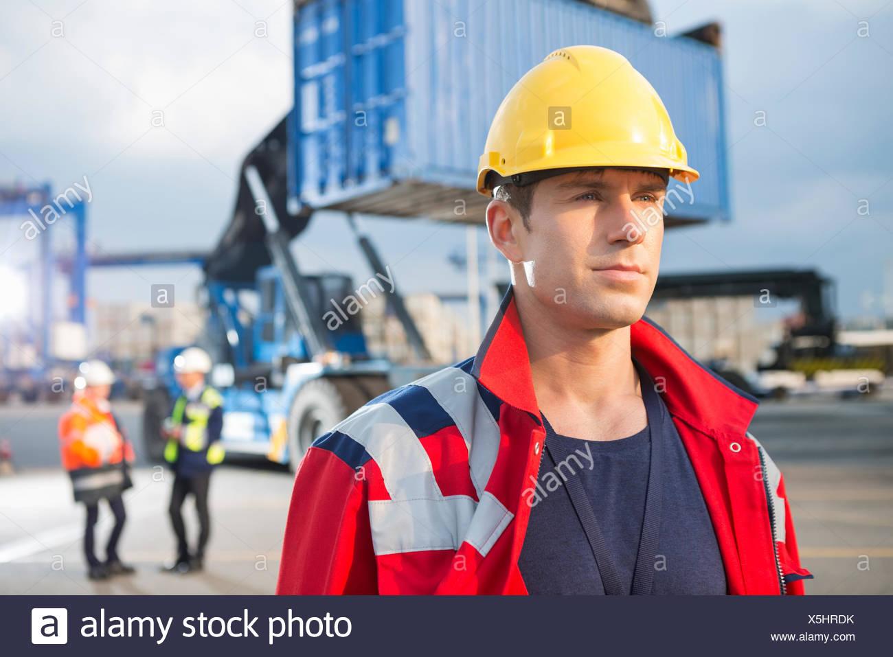 Seguros de trabajador masculino con colegas en el fondo al patio de envío Imagen De Stock