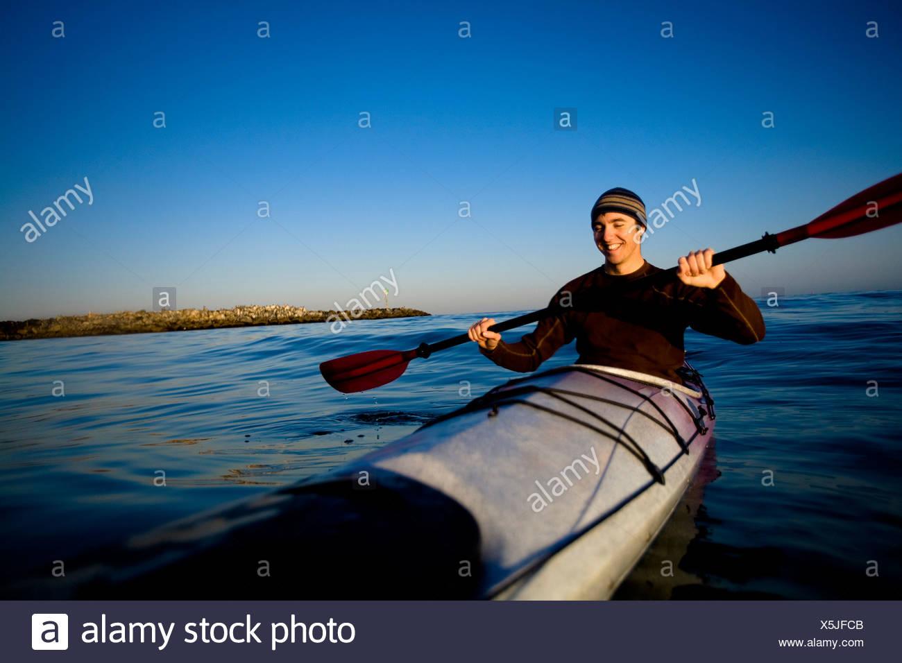 Un hombre joven sonríe mientras remando un kayak de travesía, justo en las afueras de Ventura Harbor en Ventura, California. Imagen De Stock