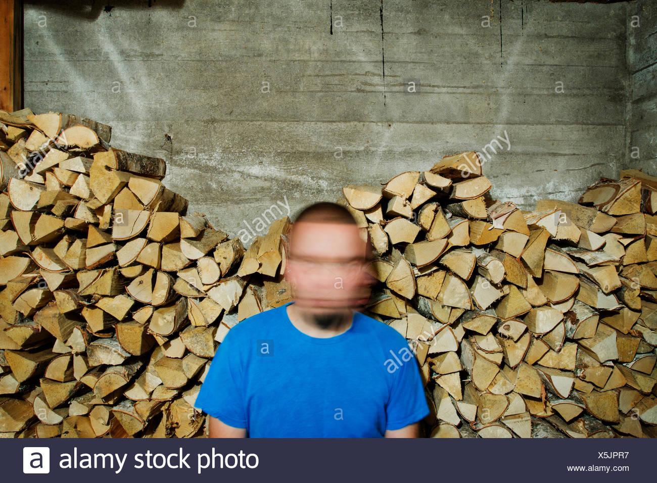 Finlandia, Heinola, el hombre con la cara borrosa contra el montón de madera Foto de stock