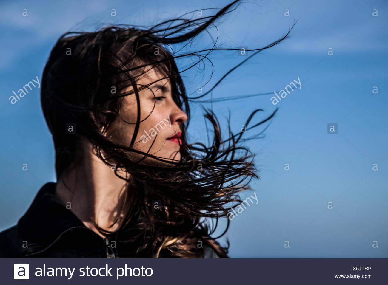 Mujer joven busca lateralmente con pelo en el viento Imagen De Stock