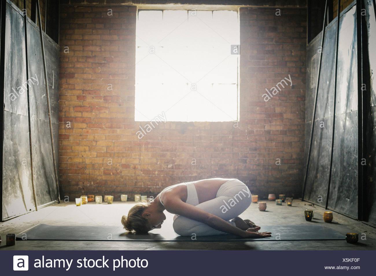 Una mujer rubia en una cosecha blanca top y leggings,arrodillado sobre una alfombrilla en el suelo, rodeado de velas. Imagen De Stock
