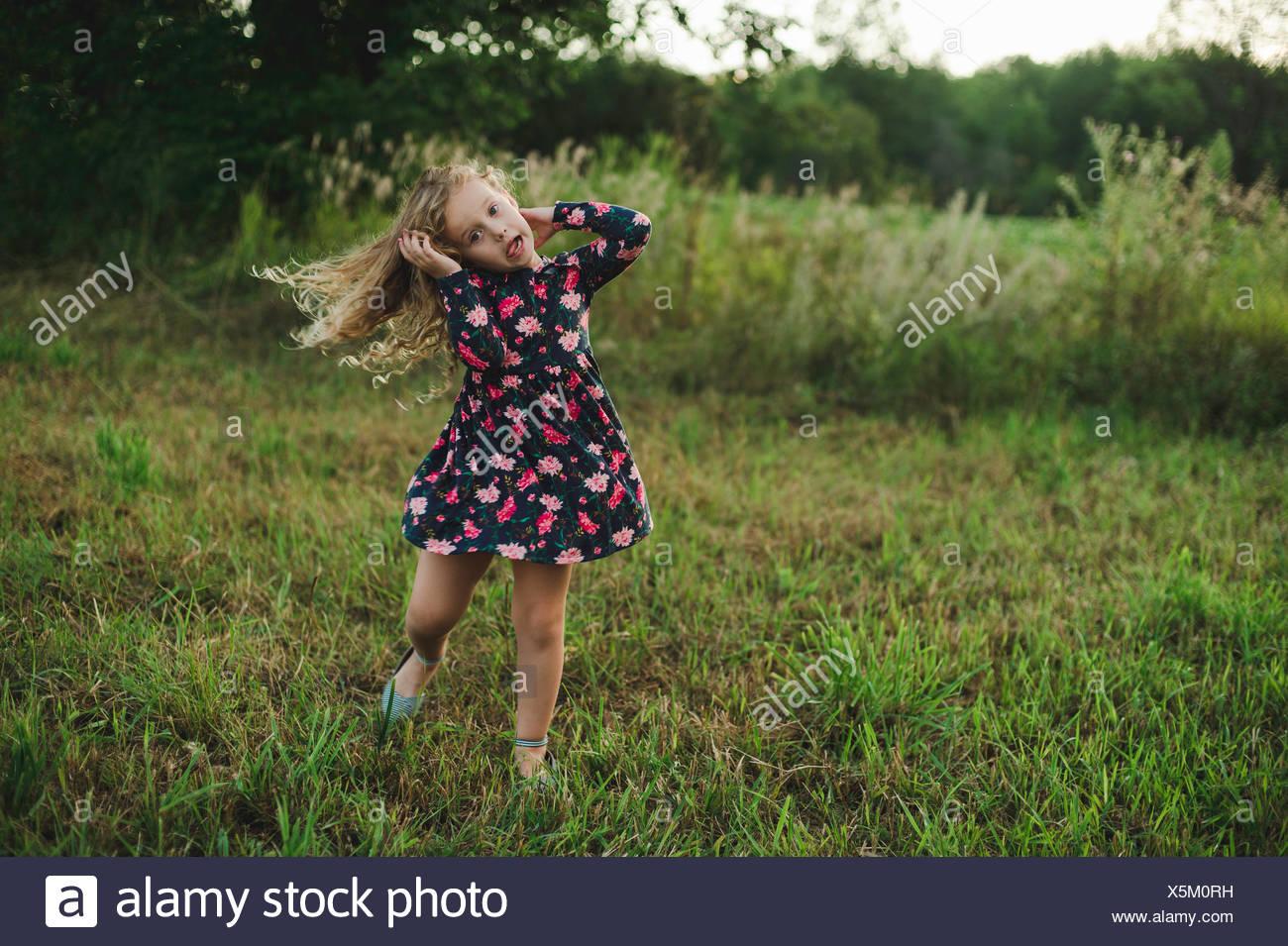 Rubio chica corriendo y tirando de un rostro en el campo Imagen De Stock