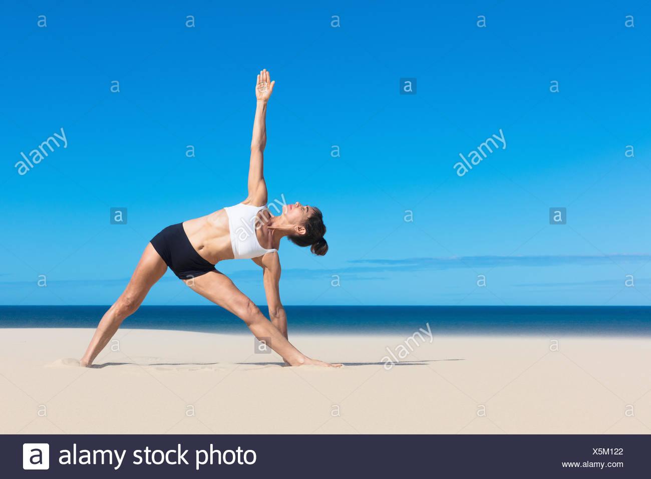 Mujer en la playa doblado lateralmente los brazos levantados en posición de yoga Imagen De Stock