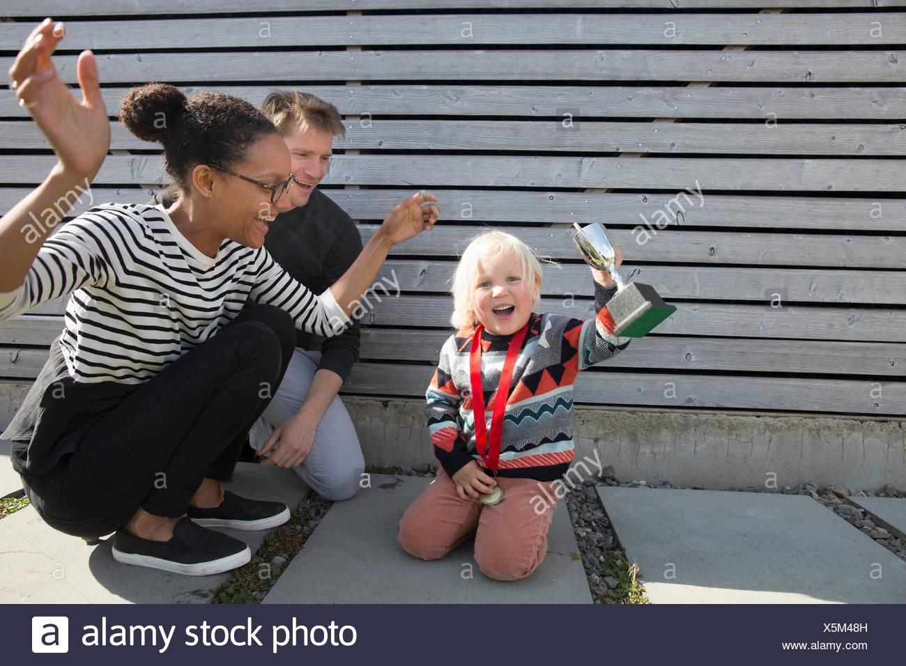 Niño sosteniendo el trofeo, madre vítores Imagen De Stock