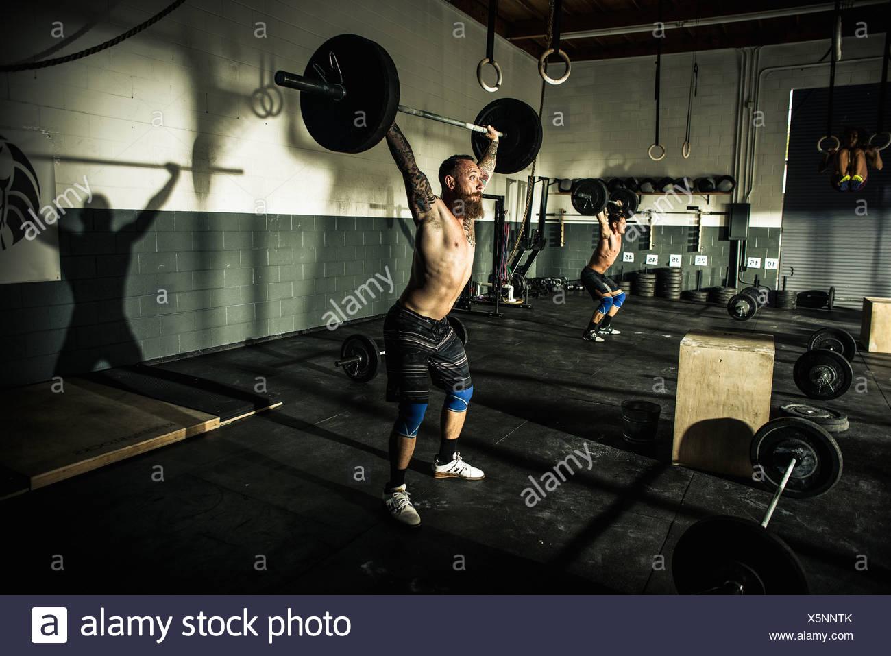Dos hombres en el gymnasium barbels elevación Imagen De Stock