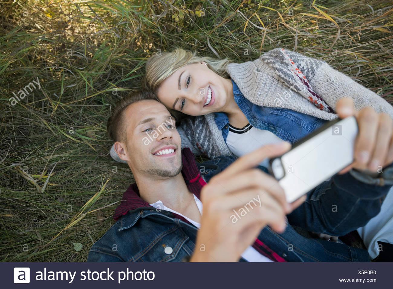 Par sentar en la hierba tomando selfie Imagen De Stock