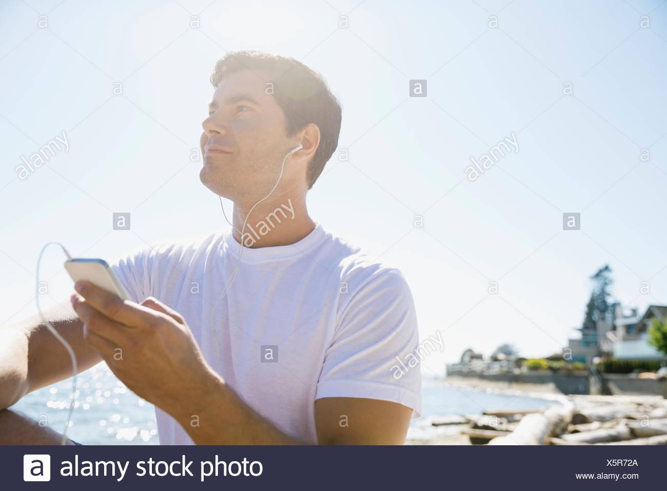 Runner escuchar el reproductor de mp3 en la playa Imagen De Stock