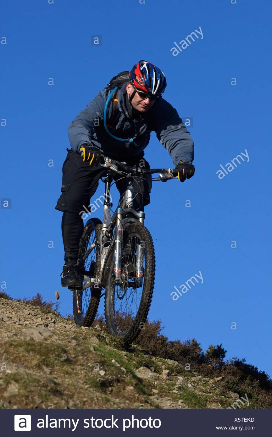 Ciclista de montaña equitación colina abajo. Foto de stock