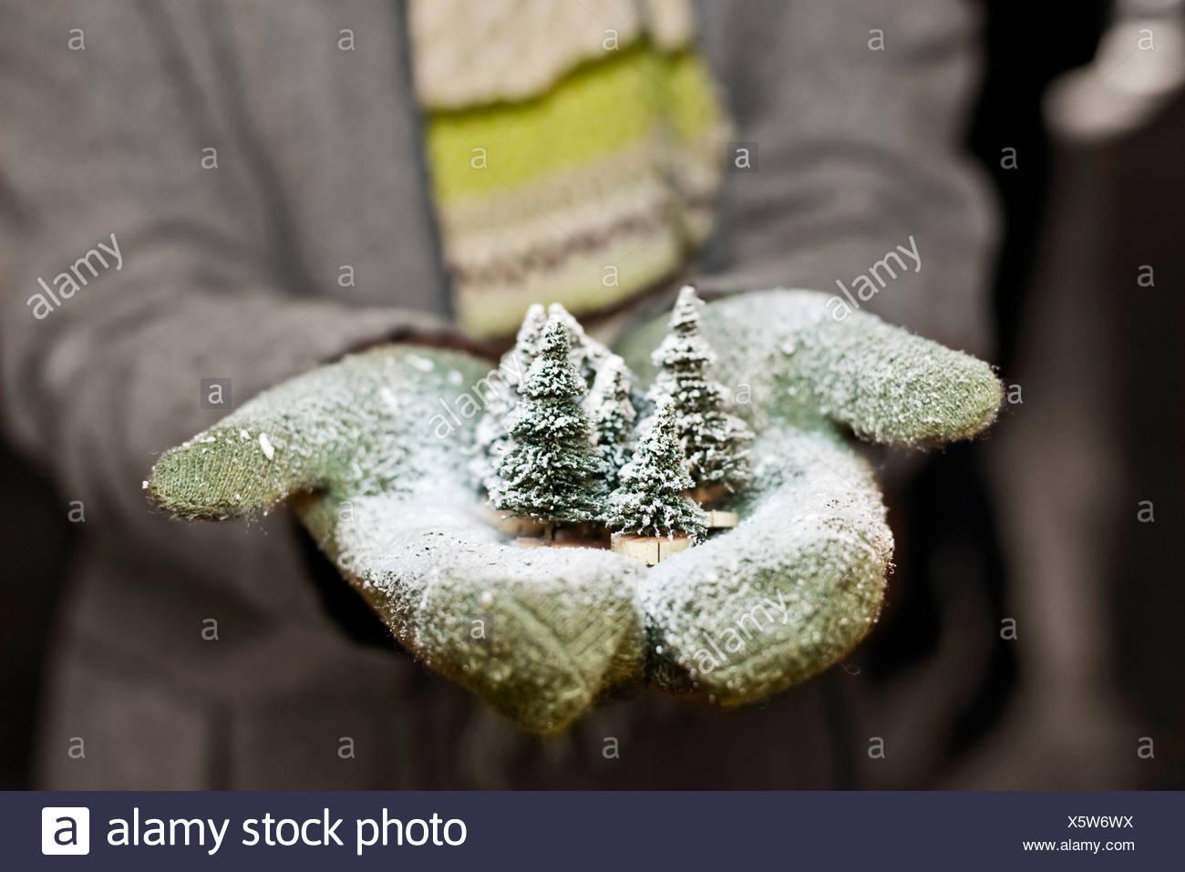 Mujer joven con guantes mantiene la decoración navideña, vista parcial Imagen De Stock