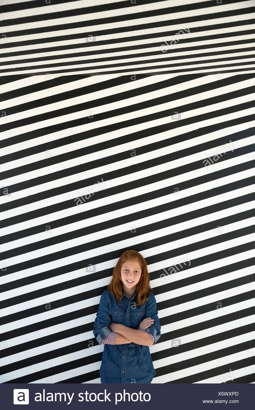 Retrato chica contra la pared a rayas en blanco y negro Imagen De Stock