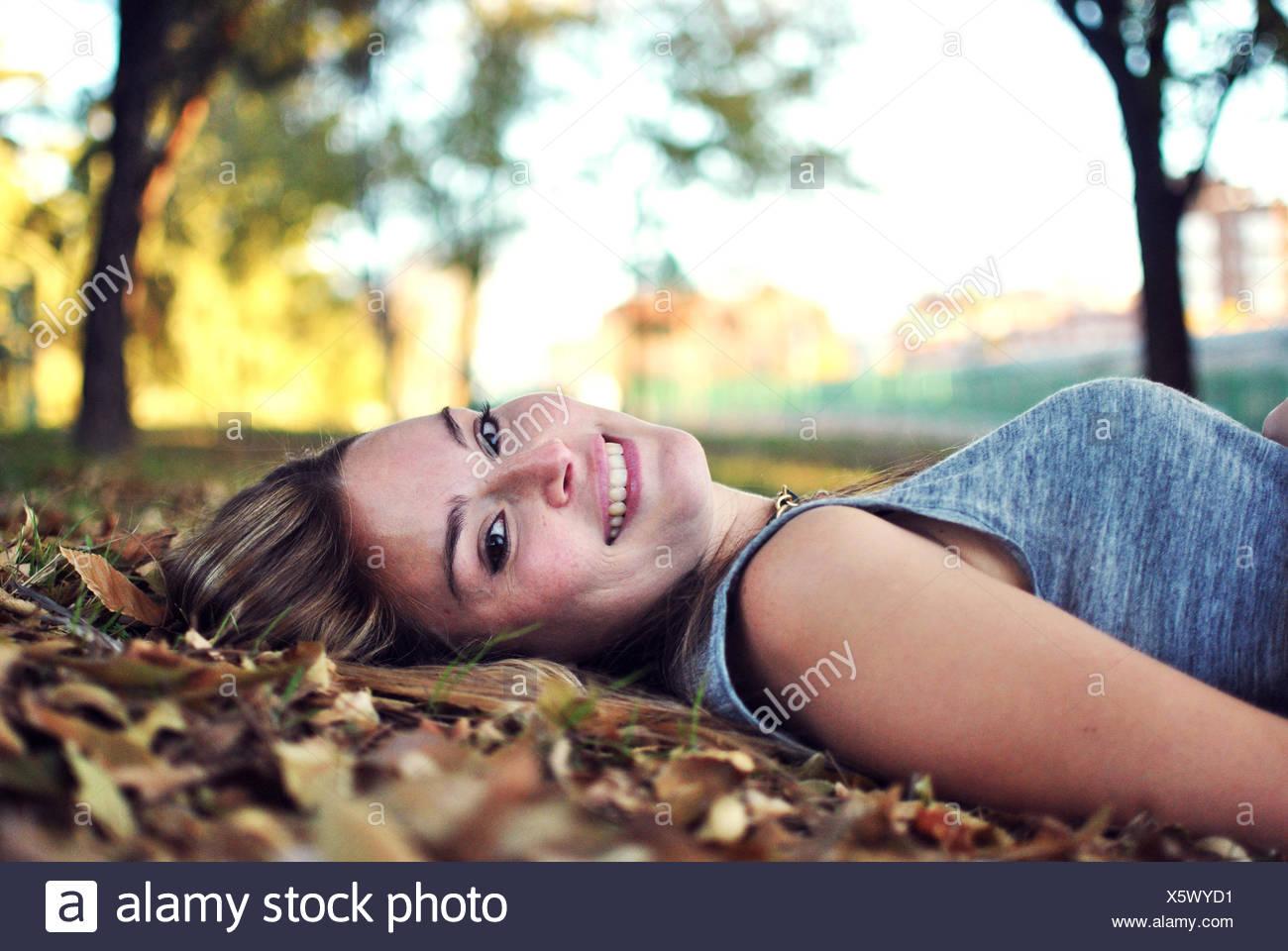 Retrato de mujer sonriente tumbado sobre hojas de otoño Foto de stock