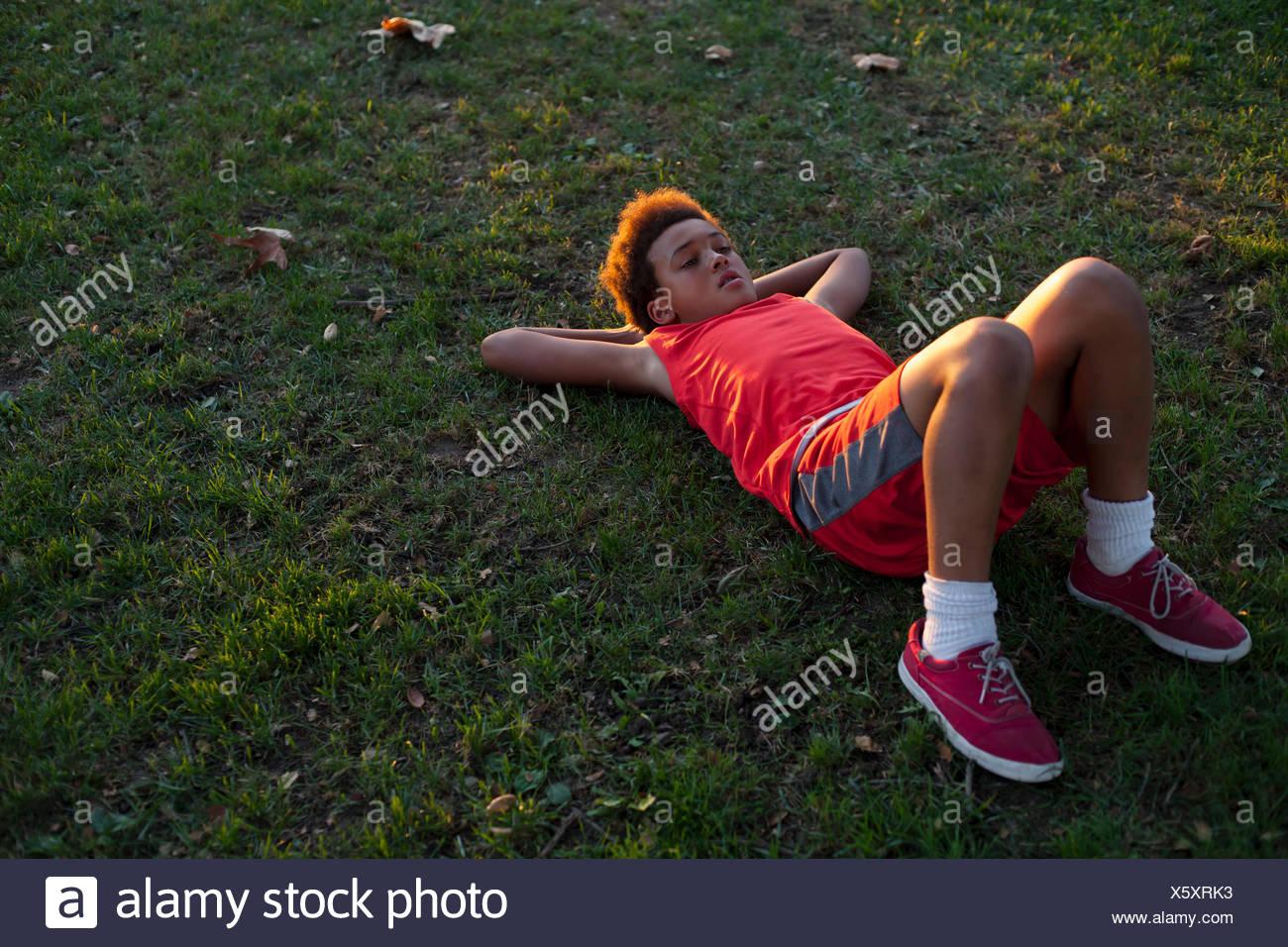 Triste looking boy acostado sobre la espalda en el parque Imagen De Stock